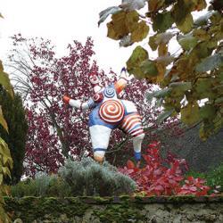 Nana rouge et bleue en situation au dessus d'un mur entre un cotinus rouge et des santolines grises mettant en valeur les couleurs vives de la sculpture